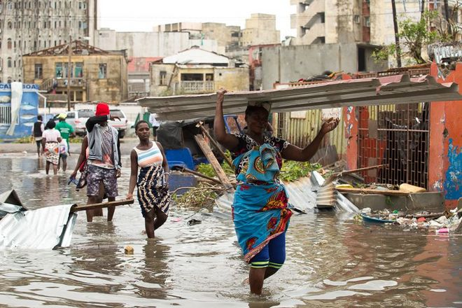 IDAI Aftermath - People carry their personal effects through a flooded section of Praia Nova in Beira after the cyclone